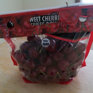 Plastic bag filled with cherries and labeled with the PLU number.