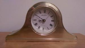 Shiny brass analog clock.