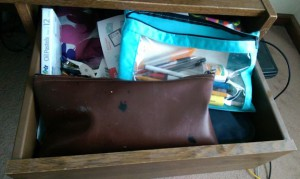 Desk drawer full of old pencils, pens, and other junk.
