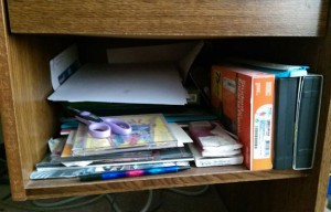 Desk shelf full of clutter.