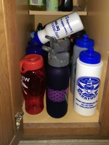 Water bottles in a cabinet, with one on top of the others.