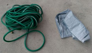 Old green hose and folded-up deflated air mattress.