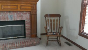 Rocking chair in corner between fireplace and window.