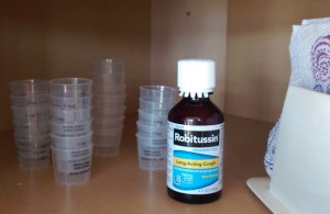 Four stacks of old plastic cough syrup dose cups.