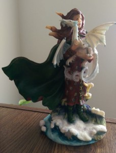 Figurine of fairy holding small white dragon.