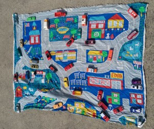 Toy cars arranged on fabric with pictures of roads and buildings.