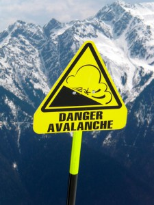 Avalanche warning sign with mountains in background