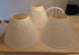 Three old worn-out lampshades on a table.