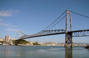 Long suspension bridge with city in background.
