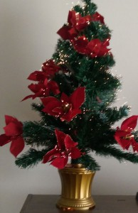 Small artificial holiday tree with red flowers and fiber-optic lights.