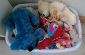Laundry basket full of dog toys and stuffed animals.
