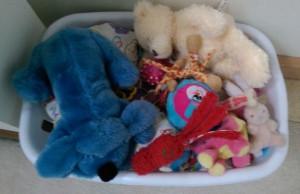 Laundry basket full of dog toys and stuffed animals.