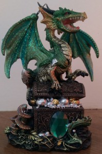 Figurine of a green dragon on a treasure chest.
