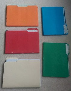 Five old file folders with bank statements in them.