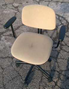 Old desk chair in the parking lot of the thrift store.