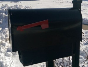 New black mailbox on post, with snow all around.