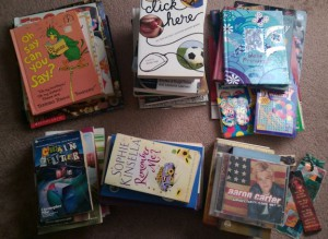 Stacks of children's books and other bookcase clutter.