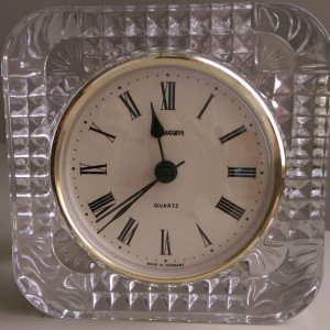 Old clock with analog face in clear plastic case.