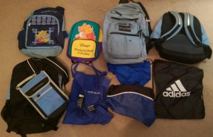 Two rows of old backpacks on brown carpet.