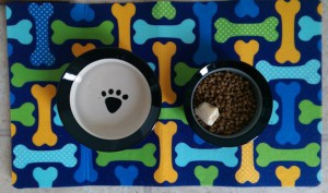 Ceramic food and water bowls for the dog, on a mat decorated with brightly colored bones.