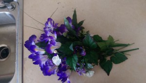 Bunch of fake flowers, mostly purple iris, next to my sink.