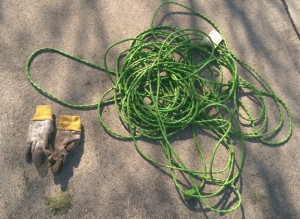 Old green extension cord and grimy gardening gloves.