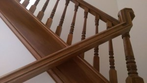 View of wooden banister looking up from lower handrail to upper portion of stairway.