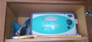 Blue and white plastic Easy-Bake toy oven on a kitchen cabinet shelf, with its accessories.