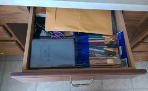 Desk drawer under kitchen counter, full of random stuff.