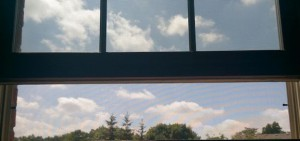 Open window with view of treetops and small white clouds.