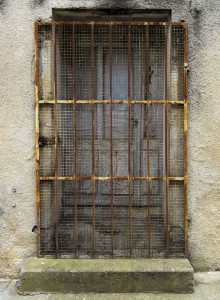 Scary-looking door set into crumbling concrete with rusty bars and a screen covering it.