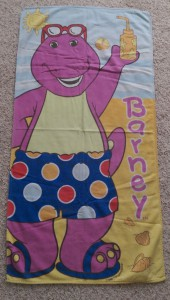 Child's towel with Barney the dinosaur in beach clothing.