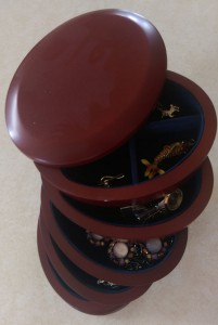 Oval wooden jewelry box with five rotating vertical drawers, partly open.