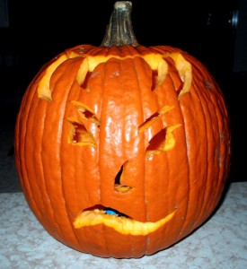 Pumpkin with carved face and skeptical expression.