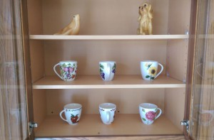 Kitchen cabinet with three shelves and glass doors, open to show brightly painted mugs and candle-wax animal figurines.