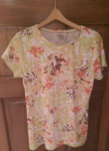 Short-sleeved blouse with an autumn leaf pattern in pale green, rust red, and shades of brown.