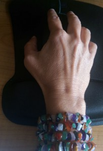My hand on a mousepad with crystal beads wrapped around my wrist four times.
