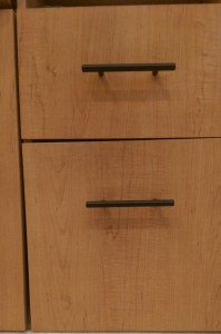 Two sturdy black drawer pulls on a wooden desk.