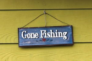 "Wooden sign ""Gone Fishing"" hanging on a wall with wooden siding."