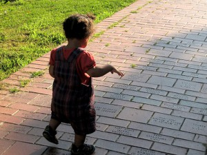 Toddler taking steps on a brick walkway.