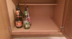 Mostly empty bottles of liquor in a cabinet.