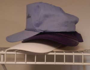 Stack of hats on a closet shelf.