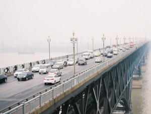 Cars crossing a bridge on a foggy day.