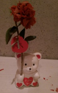 "Ceramic bear with ""I Love You"" on its chest, holding a decayed fake flower."
