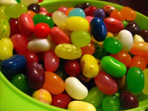 Jellybeans of different colors in a green plastic bowl.