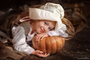 Girl dressed as Cinderella in old-fashioned clothing with a pumpkin.