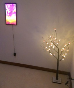 Flat screen digital art hanging on wall, with small Christmas tree in corner.