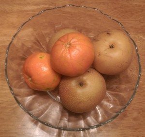Glass fruit bowl with large mandarin oranges and Asian pears.