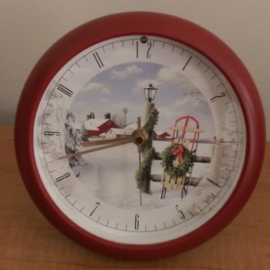 Analog clock with a red frame and a wintery holiday picture in the middle.