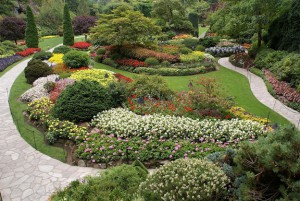 Garden with flowers, shrubs, and winding stone paths.